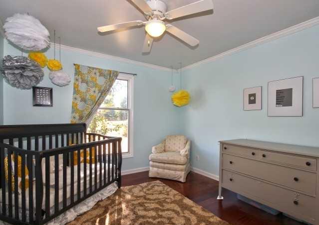 nursery with light blue walls hardwood floors