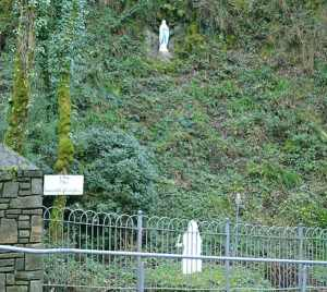 The Holy Well/Grotto near to Mount Melleray Abbey with a statue of Our Lady of Lourdes high on the cliff face and a statue of St Bernadette below near the stream - The Irish Place
