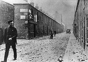 A policeman walks past the debris of a Belfast riot.