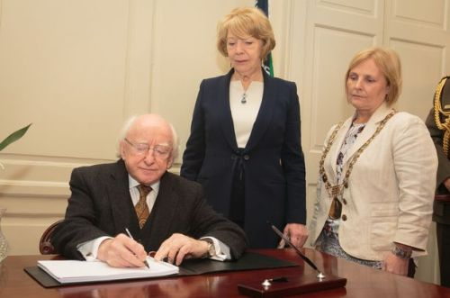 A Nation Mourns: President Michael Higgins with his wife Sabina Higgins in the Mansion House as they sign the book of condolences for the victims of the Carrickmines fire.