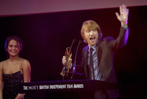 LONDON, ENGLAND - DECEMBER 06: Actress Alicia Vikander (L) and actor Domhnall Gleeson on stage as he accepts the award for Best Supporting Actor on behalf of his father Brendan Gleeson for his role in the film 'Brooklyn' at The Moet British Independent Film Awards 2015 on December 6, 2015 in London, United Kingdom. (Photo by John Phillips/Getty Images for The Moet British Independent Film Awards) The Irish shine at BIFA Awards