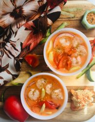 gazpacho with shrimp. vegetable cuttings and herbs on cutting board