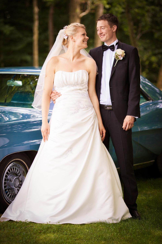 Brud og gom ved bryllupsbil