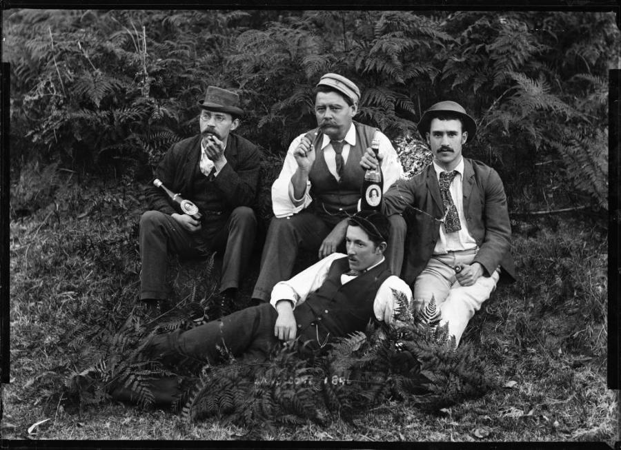 Four well-dressed men holding beer bottles