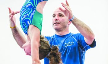 Leon Bekker, a coach, teacher and co-owner of Michigan Academy of Gymnastics in Westland, helps a student refine a move.