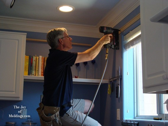 Finish trim carpenter installing kitchen moldings