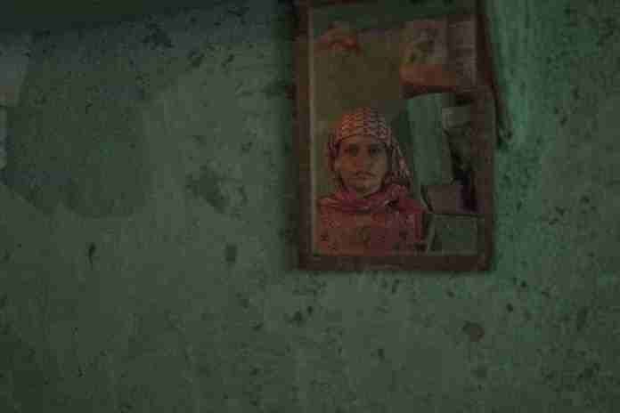 Akeel's mother staring into the mirror that has her dead son's name written with blood. Photograph by Vikar Syed