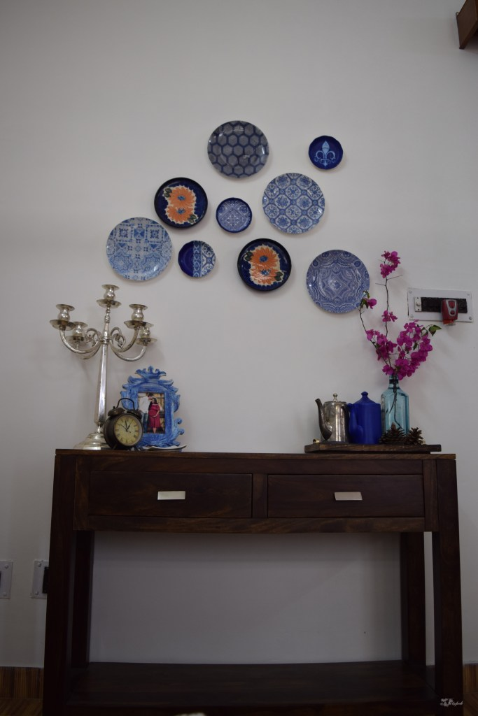 Home decor Tour by Ankita and Sitanshu's in Lucknow - The bedroom are decorated with blue frame, candlebra, assorted jugs and wall plates
