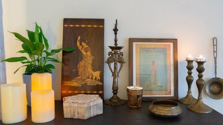 Affinity for antiques home tour of Rushika & Dipkal's - the beautiful collection of candles, frames, brass bowl, green plants, candle stands, and diya at the corner of the room