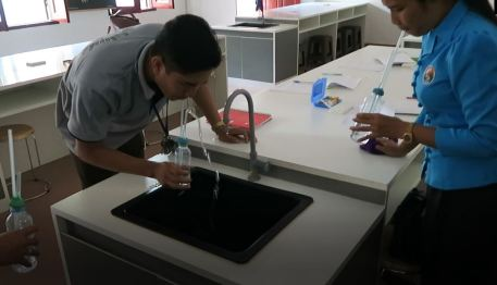Mr Sackbong Boulapane and Ms Chanmany Tippachan perform the experiment over the sink.