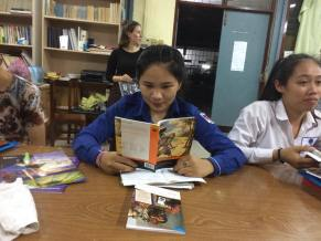 She likes to read, so she reads an English book in the school library.