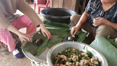Naphatsone and Aunt Thay fill the banana leaves.