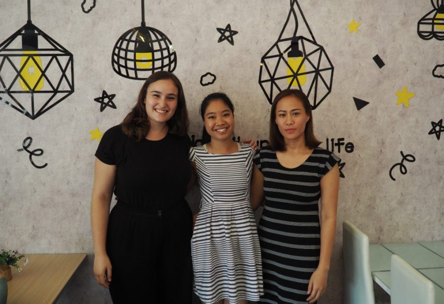 Jacqui, Phi Ha and Dit in front of one of the fun wall decorations at the café