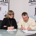Tony signing his franchise agreement with franchisor Jules White.