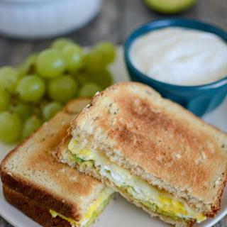 Microwave Egg Sandwich with avocado and cheese and grapes and yogurt on the side