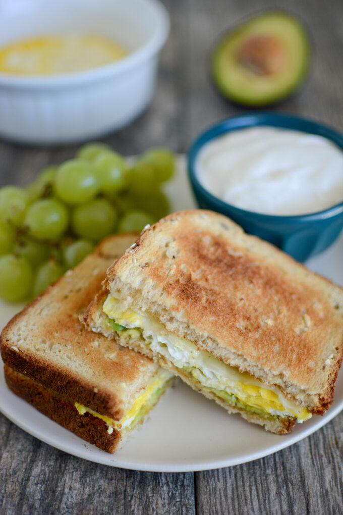 Microwave Egg Sandwich with Avocado and Cheese and Raisins and Yogurt on the Side