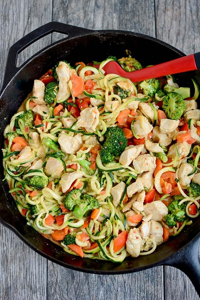 Zucchini Noodles with Chicken and Spicy Almond Butter Sauce in cast iron skillet