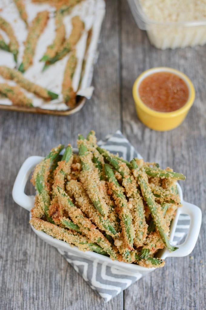 Crispy Green Bean Fries in a white dish and on a sheetpan with Italian Dressing for dipping