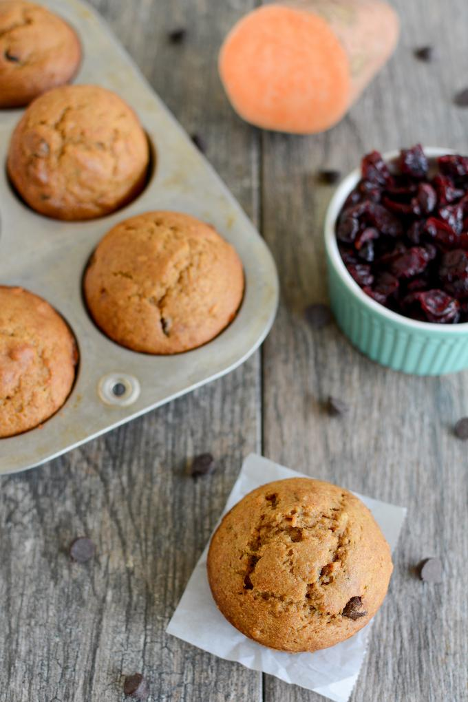 Cranberry Sweet Potato Muffins on parchment paper and in muffin tin