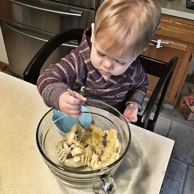toddler in the kitchen mashing banana