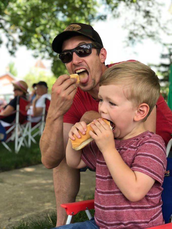dad and toddler eating hotdog