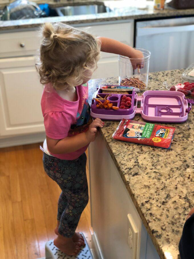 toddler reaching into pretzel jar