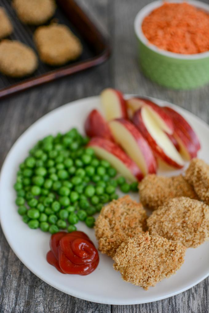 Red Lentil Chicken Nuggets with sliced apples and green beans on a white plate