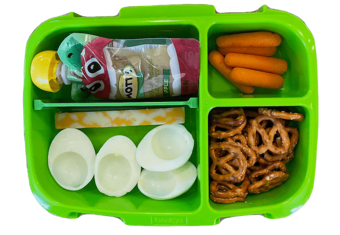 kids lunch box with applesauce, carrots, cheese stick, hard boiled egg and pretzels