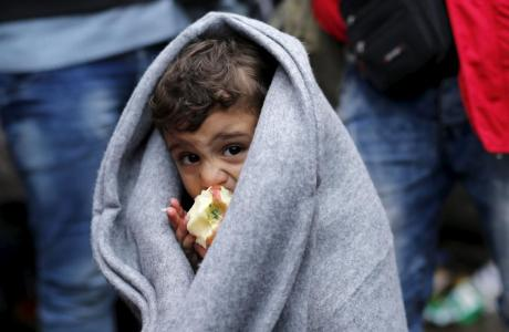 A migrant child eats an apple as he waits next to the border crossing with Croatia near the village of Berkasovo, Serbia,, October 12, 2015. REUTERS/Antonio Bronic