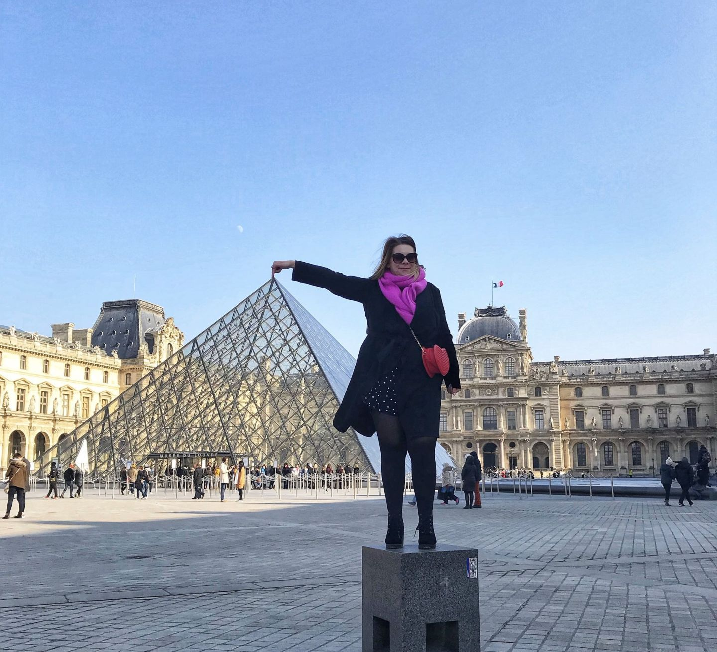 Me touching the top of the pyramid at The Louvre