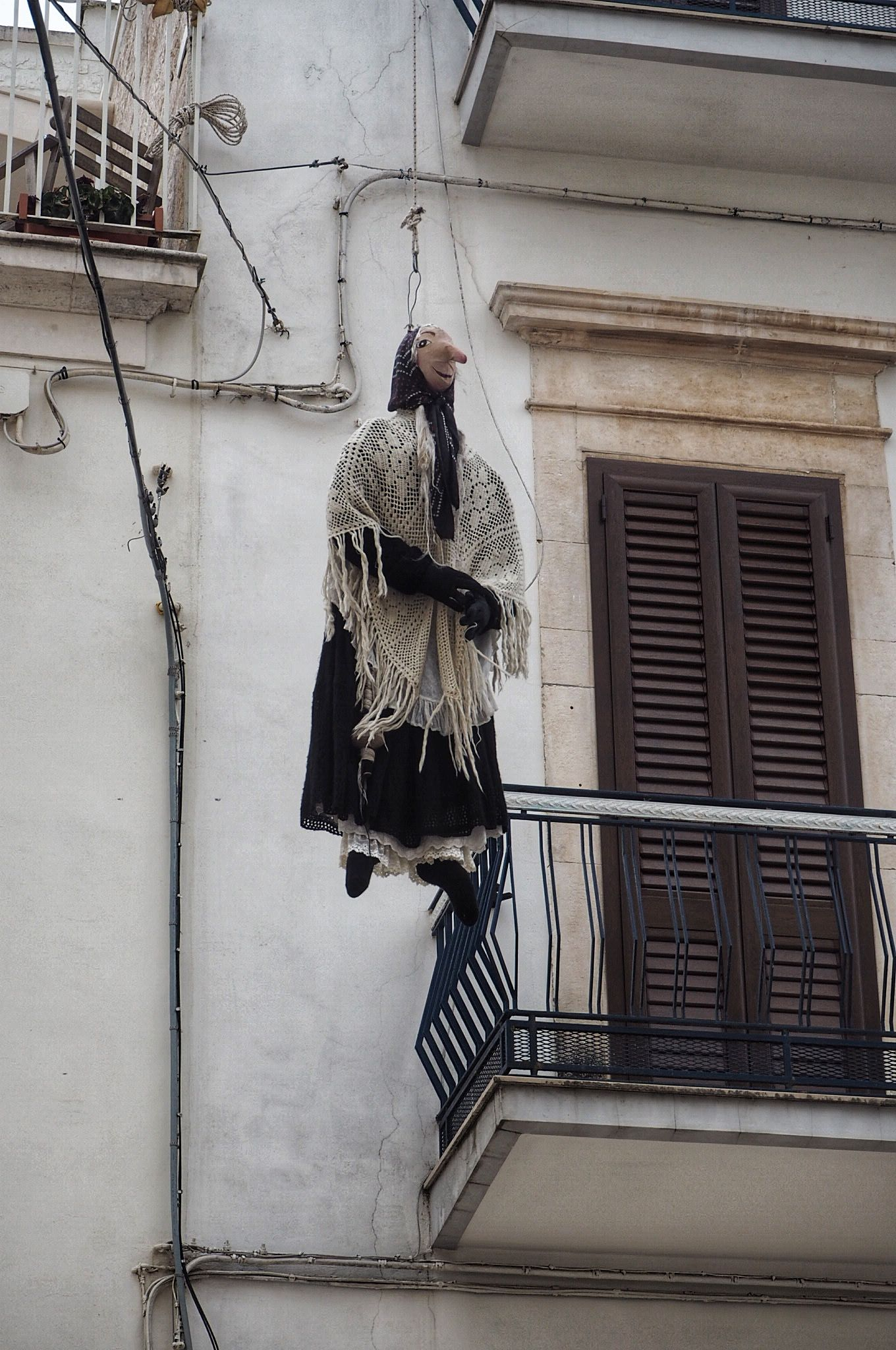 Locorotondo Quarandone lady puppet hanging from rope in town