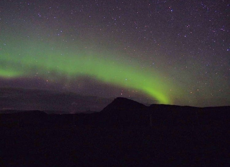 Green and purple haze of The Northern Lights Iceland on a starry night