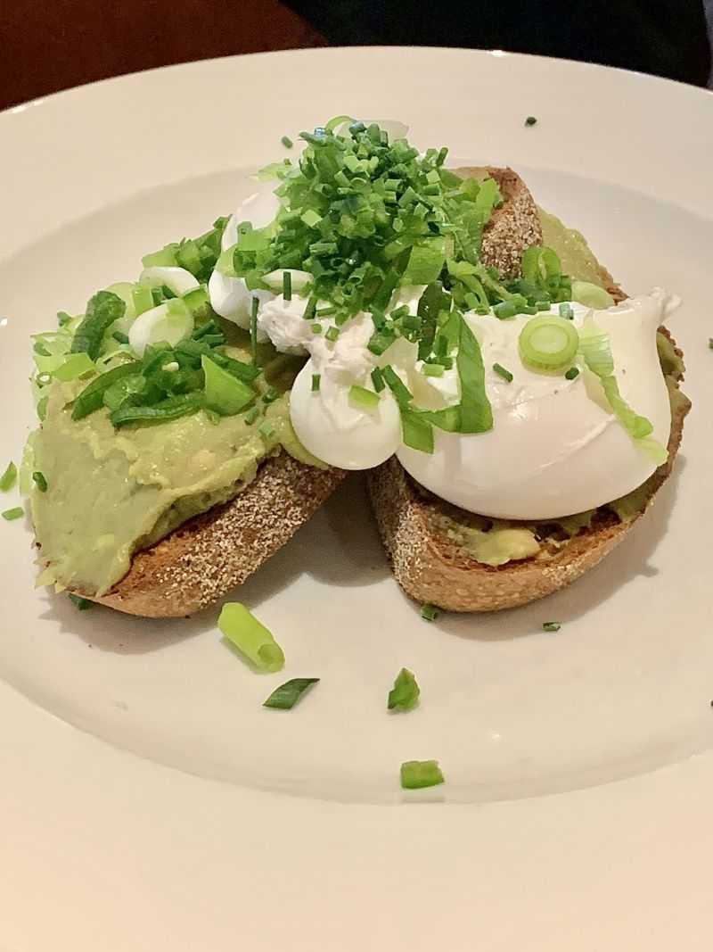 smashed avocado with free-range poached eggs, spring onion and chilli on toasted sourdough