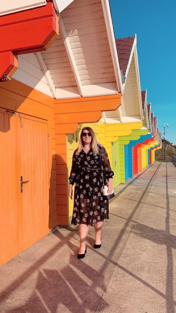 Me at the colourful beach chalets Scarborough