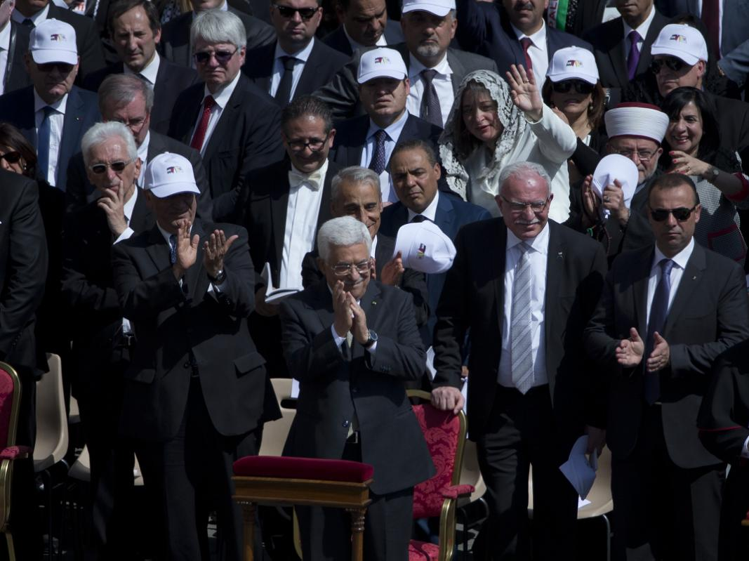 Palestinian President Mahmoud Abbas, foreground centre, applauds during a canonization ceremony of four new saints celebrated by Pope Francis in St.Peter's Square at the Vatican, Sunday, May 17, 2015.  Among the new saints are Arab nuns Sts. Mariam Bawardy and Marie Alphonsine Ghattas, who lived in what was Ottoman-ruled Palestine in the 19th century. (AP Photo/Alessandra Tarantino)