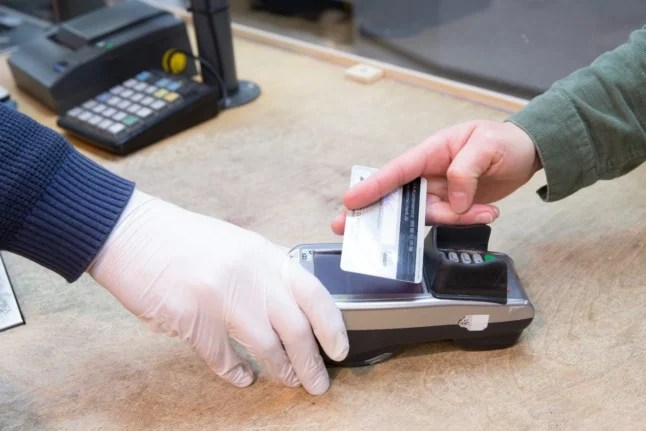 A customer pays by card in a Berlin shop.