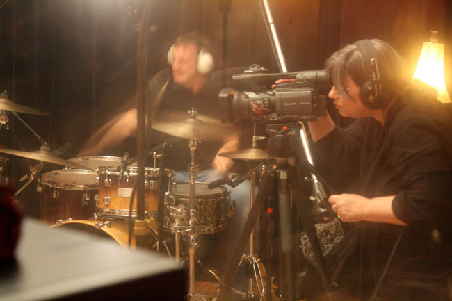Drummer Kenny Graeber of The Nonclants rocks out hard while Oxford Sounds Producer Marie Antoon films the action. Photograph by Newt Rayburn.