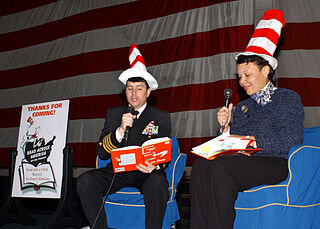 """The NEA has recently done away with the link between """"Read Across America"""" Day and Dr. Seuss' birthday because of concerns about Dr. Seuss' racism.   At sea aboard USS George Washington (CVN 73) March 1, 2002 -- Executive Officer Captain K.M. Donegan, and Ms. Princess Moss, Virginia Education Association President, read to elementary students in the ship's hangar bay during events to commemorate the national """"Read to Kids, Read Across America"""" campaign, held on the birthday of the famous kids book author Dr. Seuss. George Washington is conducting carrier qualifications off the Virginia coast. U.S. Navy photo by Photographer's Mate 3rd Class Bobbie Attaway."""