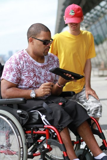 Event-photography-man-in-wheel-chair-shows-his-friend-Ipad