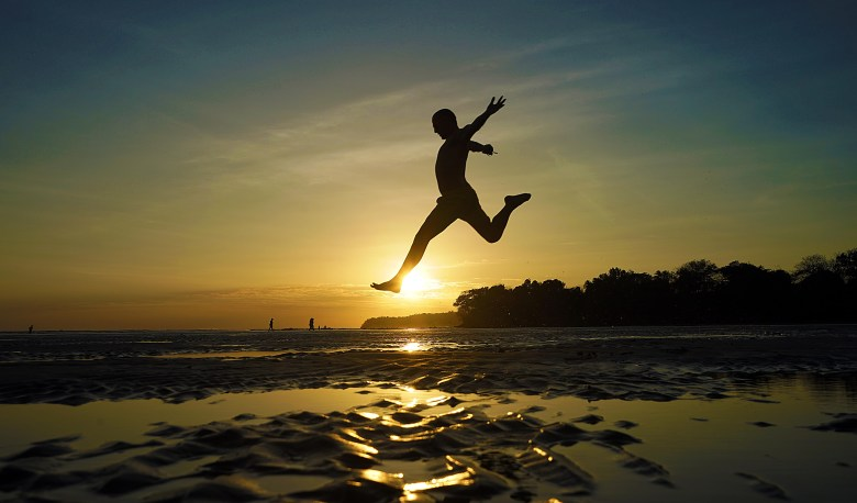 Sunset leaps on the black sand beach of Santa Catalina