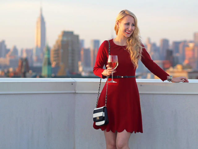 Wearing a red dress with a bow belt and striped bag with view of NYC skyline
