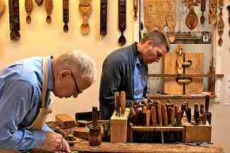 Father and son handcarving lovespoons together at The Lovespoon Workshop.