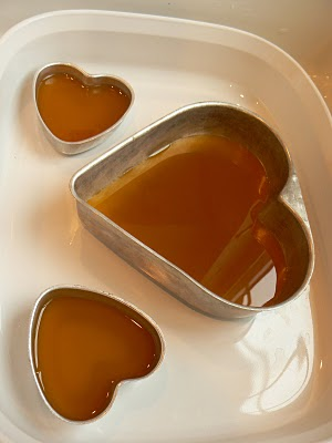 Pouring melted beeswax into the heart moulds