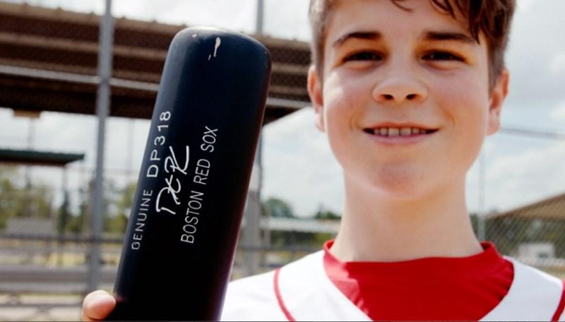 Make-A-Wish Kid Jace Andrews holds a Boston Red Sox baseball bat