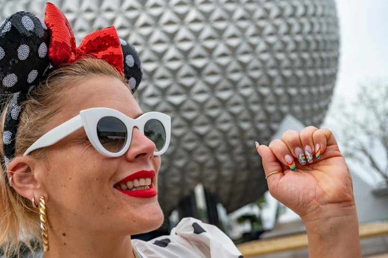 Actress Busy Philipps shows off her Disney-themed PRIDE Month nails in front of Spaceship Earth at EPCOT during a family vacation to Walt Disney World Resort