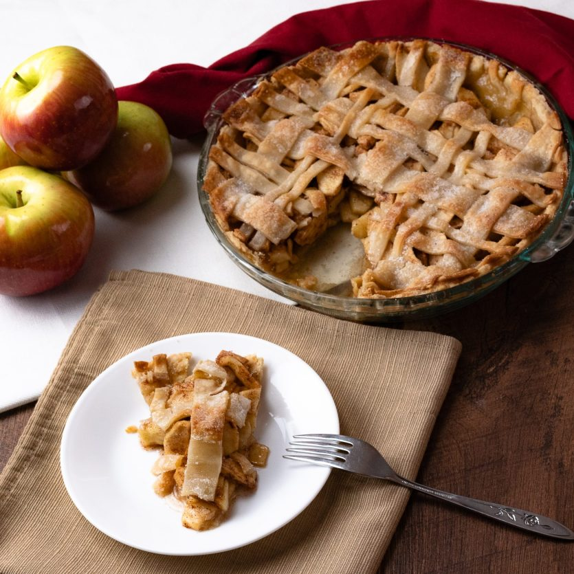 homemade apple pie, plaid, lattice crust, apples, shiny, pie dish, crisp, pie crust, white background Christmas Thanksgiving white plate brown napkin fork pie slice