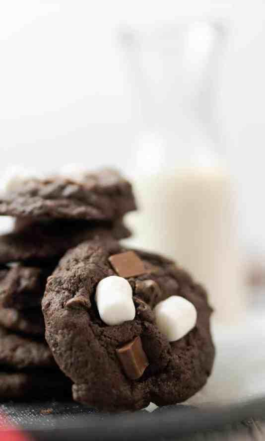 hot cocoa cookies hot chocolate mix mini marshmallows chocolate chunks glass of milk black plate baker's rack