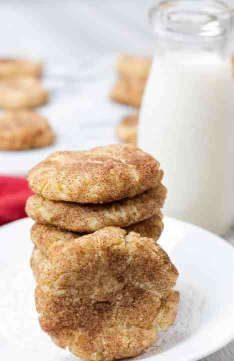 brown butter sugar cookies white plate red background cinnamon sugar sprinkles stacked glass of milk