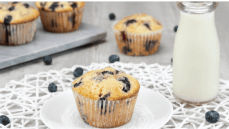 jumbo blueberry muffins glass of milk fresh blueberries gray background white plate white placemat