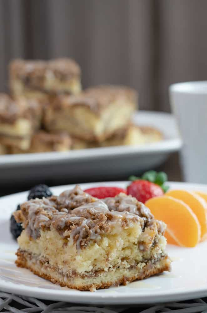 sliced coffee cake with drizzle on a white plate with blackberries, strawberries and mandarin oranges. A cup of coffee and a plate of sliced coffee cake.